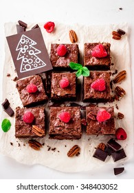 Brownie pieces with nuts decorated with berries and mint leaves, christmas card on the white paper. Selective focus.