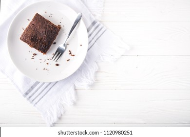 Brownie slice on a white plate on white napkin on white wooden background. Copy space. Flat lay. Overhead