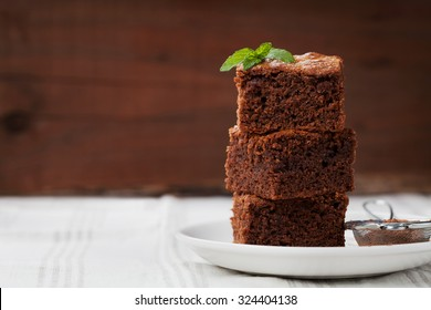 Brownie stack, closeup chocolate cake in plate on rustic wooden table