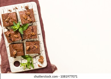 Brownie sweet chocolate dessert with walnuts and meant leaves on retro board with copy space on pastel beige background. Beautiful banner with delicious brown cocoa baked pastry.