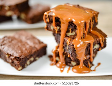 Brownies with nuts and salted caramel - Brownies on a plate sprinkled with caramel - Stretching caramel on the cake