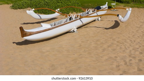 Brown-n-White Outrigger Adventure Canoe on Beach Sand Waiting for Paddlers