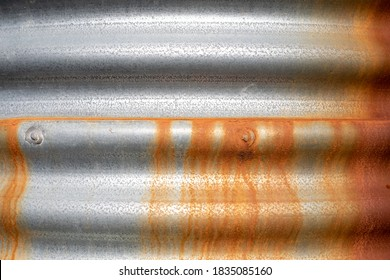 Brown/orange rust running down a silver/grey corrugated iron water tank in Victoria, Australia