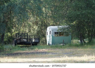 Browns Valley, California, USA. Sunday, April 25, 2021. Two trailers one flatbed and one for camping parked in a field.