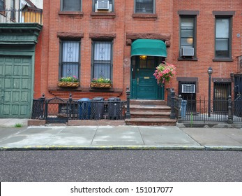 Brownstone Home with Green Awning Pink Petunias and Trash Cans lined up behind rod iron fence in Brooklyn New York USA