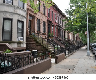 Brownstone Homes along residential Neighborhood sidewalk in Brooklyn New York on overcast sky day
