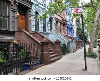 Brownstone Homes Tree Lined Urban Street with No Parking Street Cleaning Sign on Sidewalk Manhattan New York City