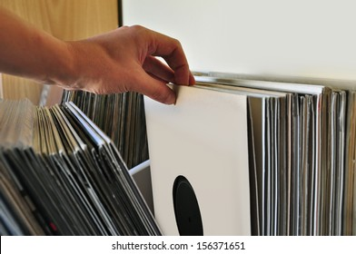 Browsing through vinyl records collection. Music background.