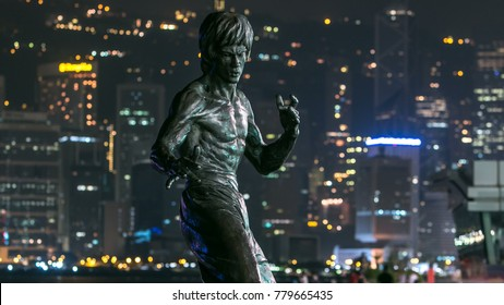Bruce Lee monument timelapse hyperlapse in the night at the Avenue of stars, modern skyscrapers at the background in Hong Kong. Bruce Lee was  the most influential and famous  martial artist of the 20