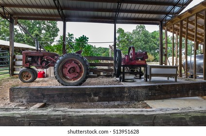 BRUCE, MISSISSIPPI. USA - SEPTEMBER 30, 2016: This is the third stage of the molasses making process. The cane is fed through the red sorghum mill.  The mill is powered by a tractor via a PTO shaft.