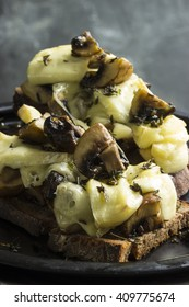 Brucette of black bread with mushrooms and cheese gratin on a black plate