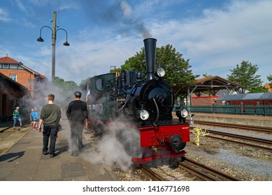 """Bruchhausen-Vilsen, Germany - May 19, 2019: the steam locomotive called """"Hoya"""" of the historic narrow-gauge railway before departure at the station on a bright sunny spring day with vivid blue sky"""