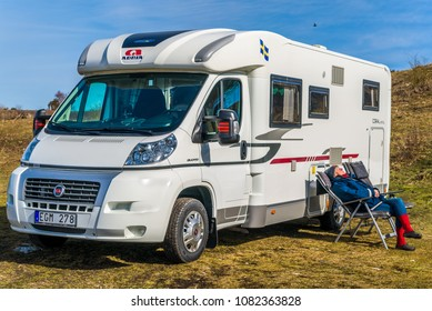 Bruddesta, Oland, Sweden - April 7, 2018: Travel documentary of everyday life and environment. Senior woman sitting outside Fiat Adria Coral S 670 SL camper enjoying the spring sun.