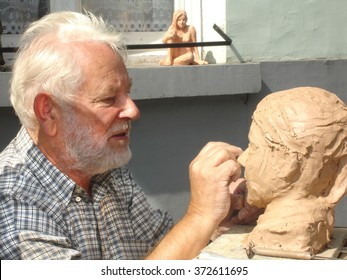 BRUGES, BELGIUM - 12 august 2006 ; Older man is creating a handmade sculpture sitting in outside in the Streets of Bruges