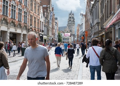 Bruges, Belgium - 13 August 2017: Tourists walking down the high street in Antwerp with Sint Salvatorskathedraal (Saint Salvador Cathedral) at the end of the street. Man in grey shirt looks at camera