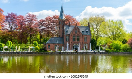 BRUGES, BELGIUM - APRIL 23, 2018: The neogothic Castle de la Faille by the Lake of Love in Bruges was built in 1893 to a design by Charles De Wulf. It was bought by the city of Bruges in 1980.