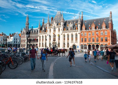 Bruges, Belgium - August 01, 2018: Market Square in Bruges. Historic buildings exteriors. Tourists walking on market square.