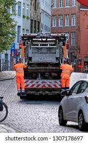 Bruges, Belgium - August 13, 2018: Yellow garbage truck or waste truck used for collection and transportation of waste or garbage.