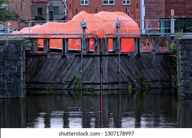 Bruges, Belgium - August 13, 2018: As part of Bruges Triennale SelgasCano studio created a floating pavilion on the Coupure Canal, clad in pink-orange vinyl and affixed with a wooden platform.