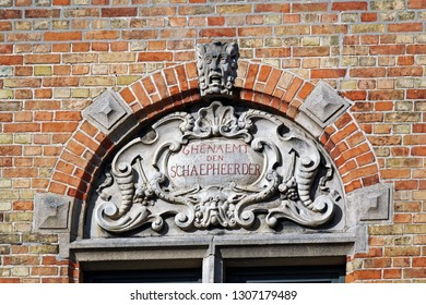 Bruges, Belgium - August 13, 2018: A stone emblem consisting of various ornaments and inscription in Dutch: Society of shepherds, decorating a historic house in the central part of Bruges, Belgium.