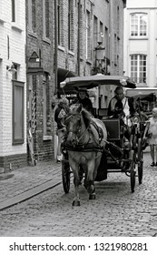 Bruges, Belgium - August 13, 2018: Tourist enjoying the popular horse drawn carriage tour along the cobbled streets of the old city centre of Bruges.