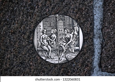 Bruges, Belgium - August 13, 2018: Circular bronze lithographs placed on a cobbled street
