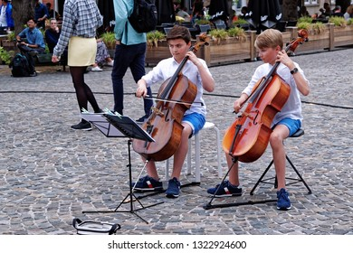 Bruges, Belgium - August 13, 2018: Two boys street performers, playing contrabass on cobbled street.