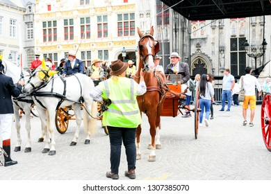 BRUGES, BELGIUM - August 15, 2018: City view with horse carriage parade with people in traditional costume and tourist at the market square. The historic city centre, World Heritage byUnesco.