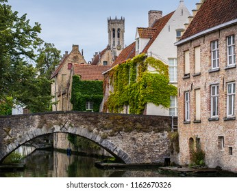 """BRUGES, BELGIUM - August 2018: Scenery with water canal in Bruges, """"Venice of the North"""", cityscape of Flanders, Belgium."""