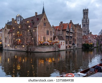 Bruges, Belgium - December 14, 2018: The Rozenhoedkaai (Quay of the Rosary) canal in Bruges with the classic medieval buildings and Belfry of Bruges in the background. Quay of Rosary in the evening.