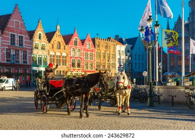 Bruges, Belgium - December 28, 2014: Horse carriage waiting tourists on Grote Markt square of Brugge Christmas. Belgian city of Bruges is UNESCO world heritage listed for its medieval center.