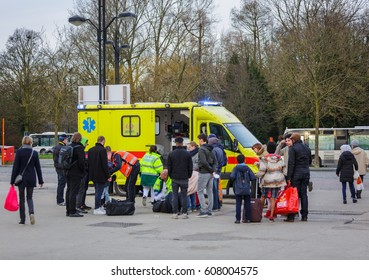 BRUGES, BELGIUM- FEBRUARY 28, 2017: Ambulance on duty helping an injured person in front of Bruges railway station.