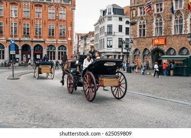 Bruges, Belgium - July 29, 2016: Horse carriage for tourists in Markt Square. The historic city centre is a World Heritage Site of UNESCO, known for his picturesque cobbled lanes and dreamy canals
