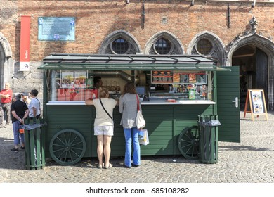 Bruges, Belgium - July 7, 2017: Tourists in front of a stand selling french fries in the market square in the center of Bruges, a beautiful medieval town in Belgium