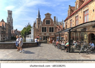 Bruges, Belgium - July 7, 2017: Tourists eating mussels and french fries in the restaurants not far from the Market Square of Bruges