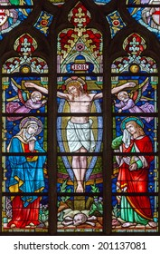 BRUGES, BELGIUM - JUNE 12, 2014: The Crucifixion on the windowpane in St. Salvator's Cathedral (Salvatorskerk) by stained glass artist Samuel Coucke (1833 - 1899).