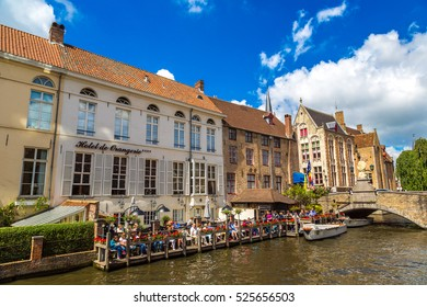 BRUGES, BELGIUM - JUNE 14, 2016: Tourist boat on canal in Bruges in a beautiful summer day, Belgium on June 14, 2016