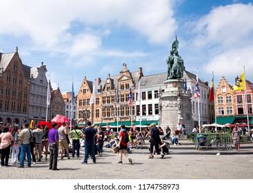 BRUGES, BELGIUM - JUNE 3,2017:  Tourists are resting on the Grote Markt square near Statue of Jan Breydel and Pieter de Coninck, Bruges.  Belgium
