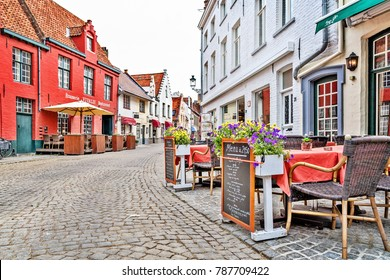 BRUGES, BELGIUM - JUNE 8, 2017: Street cafe on the ancient street of Bruges. A pavement from stone blocks, the deserted street in the morning in cloudy summer day