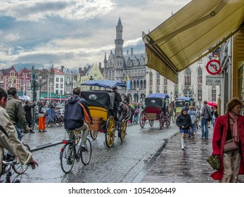 Bruges, Belgium - March 15 2015: Tourists and local Belgians crowd town square in Bruges Belgium on a rainy day as bicyclists and horse and carriages pass by on the cobblestone road.
