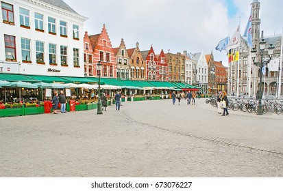 BRUGES, BELGIUM - MAY 26, 2011: Gourmet's paradise at Markt Square, various cafes and bars occupy the ground floors of old Dutch Revival mansions, surrounding Provincial Palace, on May 26 in Bruges.