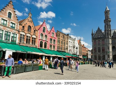 BRUGES, BELGIUM - MAY 28 2015. Tourists in north side of Grote Markt (Market Square) of Bruges, Brugge, with enchanting street cafes, meeting place of the Brugelings and tourists. Flanders.