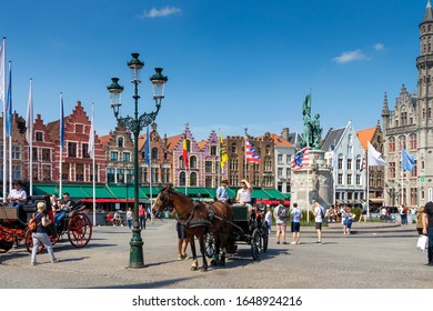 BRUGES, BELGIUM- OCT. 16, 2019 Panoramic of the colorful houses of Grote Markt Square and the typical horse carriages. Built in the 17th century, they are visited daily by thousands of tourists.