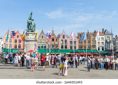 BRUGES, BELGIUM - OCTOBER 26, 2019: Panoramic of the colorful houses of the Grote Markt Square in Bruges, these are 17th century guild houses, visited daily by thousands of tourists.