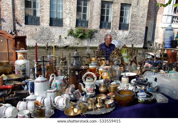 BRUGES, BELGIUM - SEPT 24, 2011 - Flea market in Bruges, Belgium. A man sells antique kitchenware and dishes