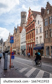 BRUGES, BELGIUM - SEPTEMBER 1, 2019: Vertical photo of bus stop, shops, bicyclist and shoppers on the cobblestoned street of Steenstraat .