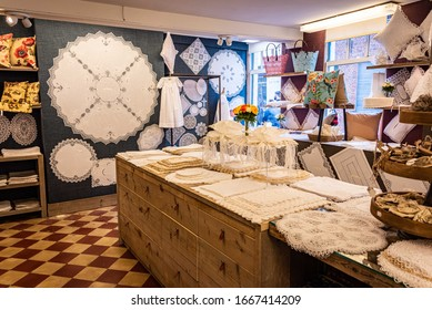 BRUGES, BELGIUM - SEPTEMBER 1, 2019: Photo of the interior of a retail lace store with checked floor, displays and counter.  Bruges lace is a fine white part lace made of cotton.