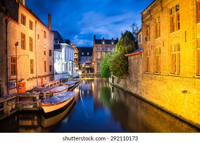Bruges, Belgium, with some canals on the foregrounds and an ancient building on the background, during evening.