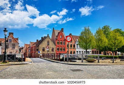 Bruges Belgium vintage stone houses and bridge over canal ancient medieval street picturesque landscape in summery sunny day with blue sky white clouds.