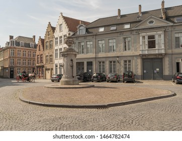 Bruges, Belgium-June 23, 2019: beautifully preserved cobblestone street with a raised cobblestone center, and an ornate stone water spigot